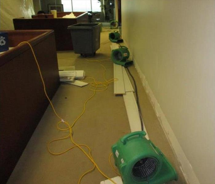 removed baseboards, carpeted floor, green air movers in an office